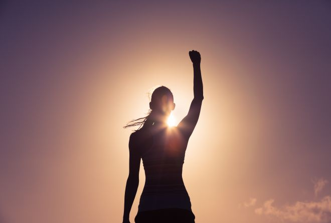 Girl with her fist in the air towards the sunset.