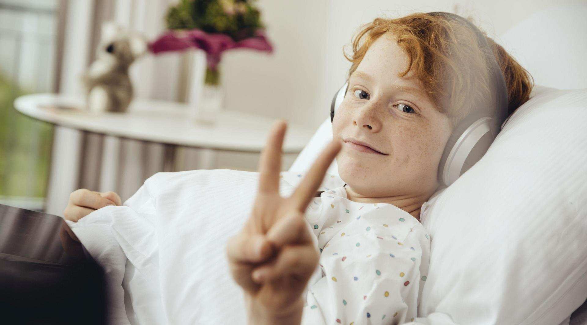 Boy in hospital bed smiling and showing peace sign.